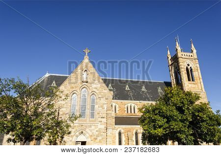 Lateral view of St Michael Cathedral, a large Gothic Revival styled sandstone building, erected in 1887 in the city of Wagga Wagga, New South Wales, Australia. poster