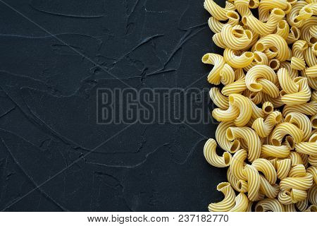 Raw Cavatappi Beautiful Decomposed Pasta With The Right, On Its Side On A Black Textured Background.