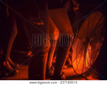 A View Of The Feet Of Young Girls Dancing In The Techno Club In Front Of A Large Fan In Red Light.