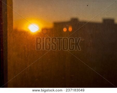 View Of Red Sunset Behind Very Dusty And Dirty Glass In The City