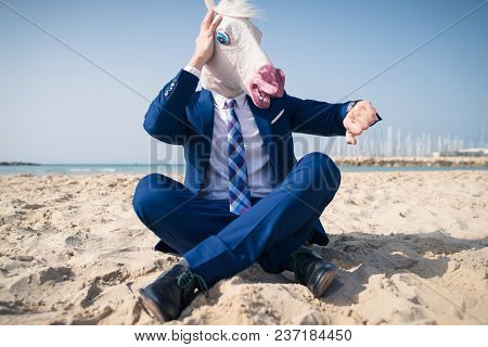 Stylish Manager In Comical Mask And Elegant Suit Sits On Beach And Looks On The Watch. Scared Man Lo