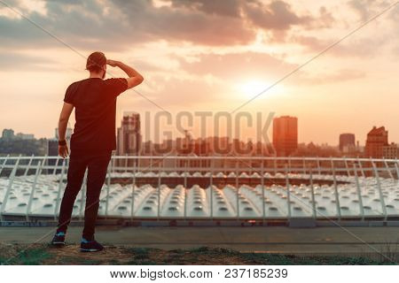Backwards Guy Looking At Sunrise Skyline Over A Seaside City