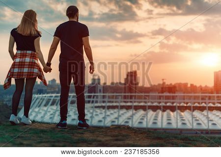 Two Lovers Embracing Overlooking The City At Sunrise Sunset. Romantic Setting.