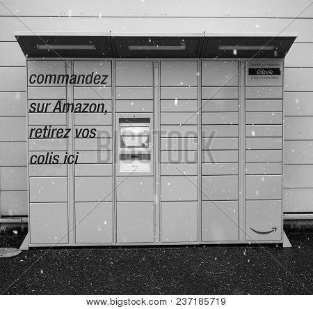 Lyon, France - Feb 4, 2017: Snowing In Front Of Modern Amazon Locker Orange Delivery Parcel Package