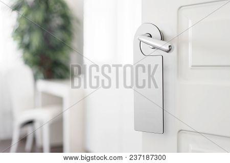Door Knob With Empty Label On A Door Handle For Your Text. Empty White Flyer Mockup Hang On Door Han