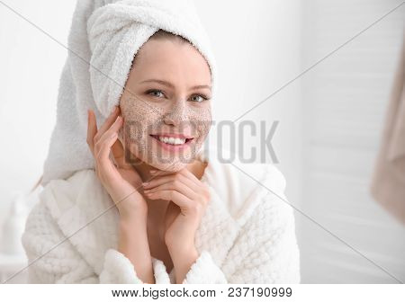 Woman With Scrub On Face In Bathroom