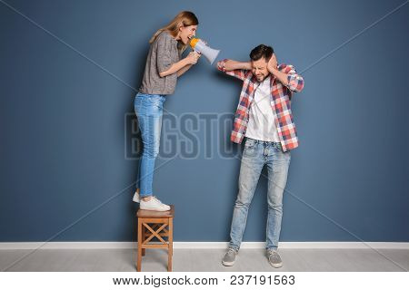 Young Woman With Megaphone Shouting At Man On Color Background