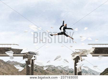 Business Woman Jumping Over Gap In Bridge Among Flying Paper Planes As Symbol Of Overcoming Challeng