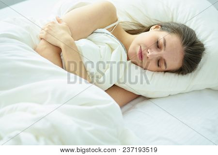 Young Beauty Asleep In A White Bed.