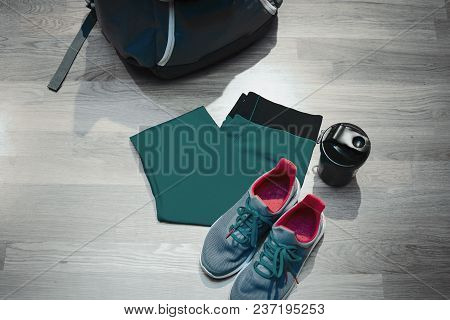 Girls Sport Shoes And Sport Mug Stand Next To Blue Sports Wear . And Backpack. Sport Equipment Is On