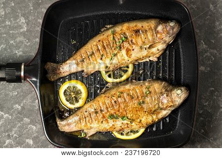 Two Trout Grilled In Frying Pan. Dietary And Healthy Food