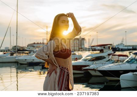 Luxurious Long-haired Girl In Stylish Summer Clothes Posing In The Seaport In The Rays Of The Evenin
