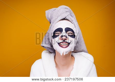 A Funny Young Girl With A Towel On Her Head And A White Bathrobe Smiles, On Her Face A Mask With A P