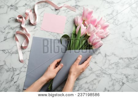 Female Florist Creating Beautiful Tulip Bouquet For Mother's Day At Table