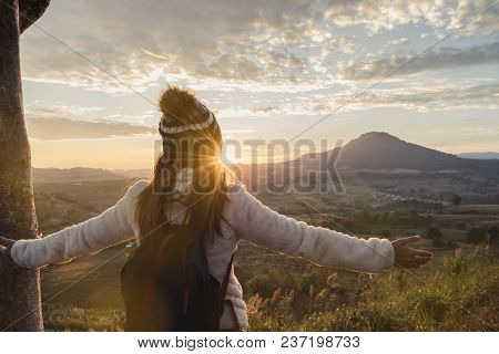 Cheering Young Woman Traveler Looking At Sunrise Over The Mountain