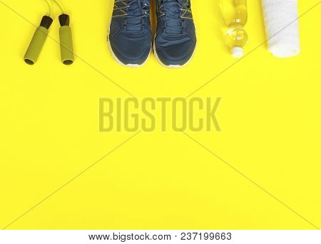 Sport Shoes, Skipping Rope And Bottle Of Water On Yellow Background. Sport And Healthy Life Concept.