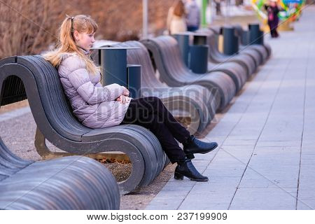 the young girl sits on a bench in the park