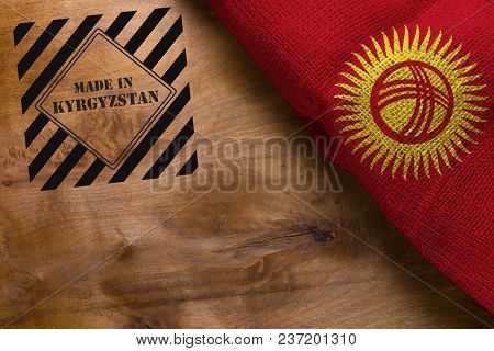 The National Flag Of Kyrgyzstan On A Wooden Surface And Stamp Made In