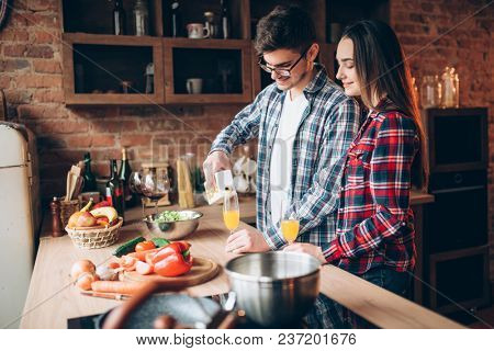 Husband pours fruit juice in glass, family cooking