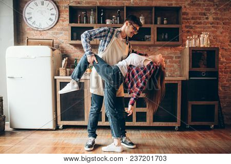 Playful love couple poses on the kitchen