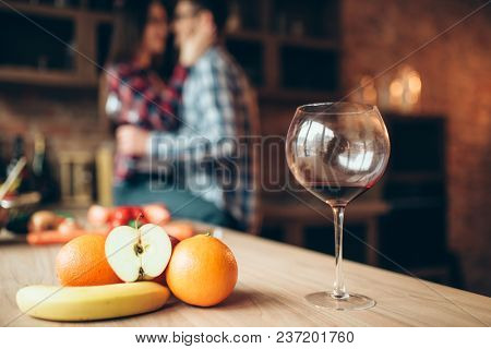 Unfinished glass of wine, fruits, couple kissing
