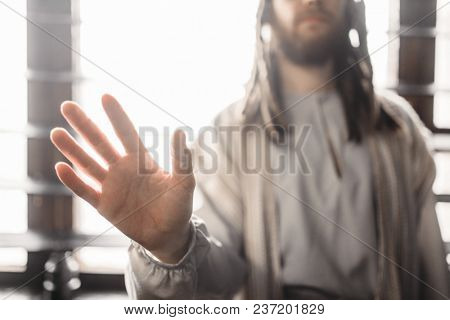 Jesus Christ reaching out his hand, peace symbol