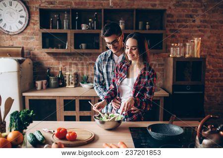 Love couple cooking on kitchen, salad preparation