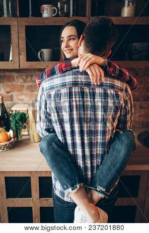 Young love couple hugs on the kitchen