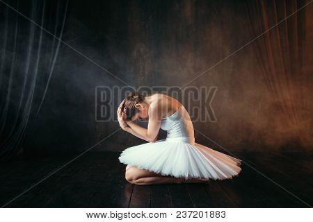 Ballerina in white dress sitting on stage