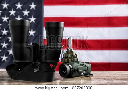 Military Monocular, Binocular And Grenade On Table Against American Flag Background
