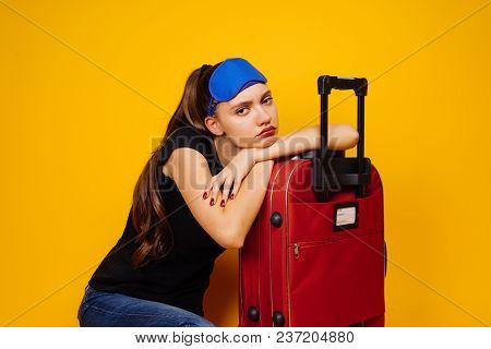 A Tired Young Girl Is Going On A Trip With A Big Red Suitcase, Waiting For Her Plane For A Long Time