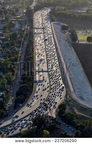 Vertical aerial view of afternoon traffic on the 12 lane Ventura Freeway passing the Sepulveda Basin in the San Fernando Valley area of Los Angeles, California.