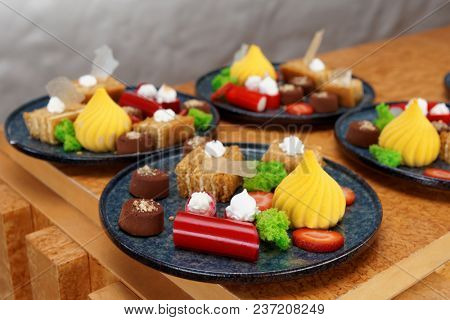 Assortment of desserts in plates on counter, catering