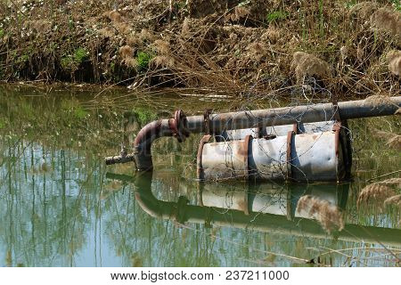 Sewage Pipe In The Lake On Floating Barrels.