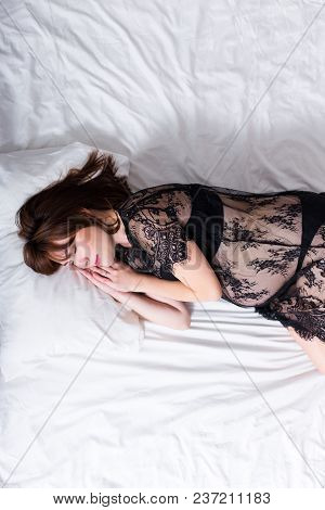 Top View Of Smiling Pregnant Woman In Black Lace Lingerie Sleeping In Bed - Copy Space