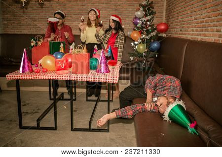 Picture Of Asian Man Are Very Drunk And Sleeping On The Sofa With His Friend Are Drinking Champagne