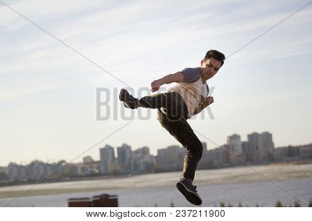 Young Man Fighter Performs Acrobatic Kick In Front Of Skylineyoung Male Kick Fighter Performs Acroba