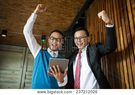 Two Asian Businessman Stand And Looking At Tablet, They Cheerful And Celebrated His Successful In Mi