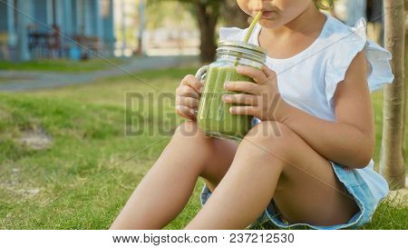 Close-up Of Cute Little Girl Drinks A Smoothies Outdoor. Crop Image Of Child Sits On Lawn And Drinki