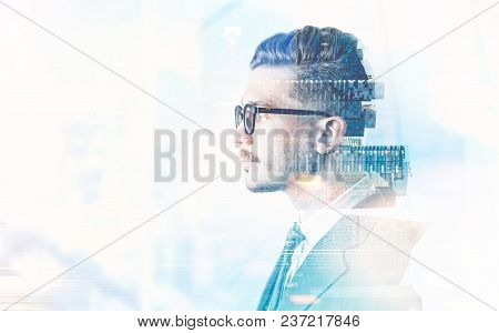 Side View Of A Bearded Young Businessman In Glasses Standing Against A Foggy Cityscape Background. T