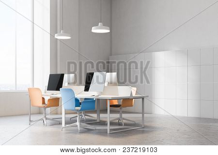 Orange And Blue Chairs Open Office Corner With A Conrete Floor, Rows Of Computer Desks And Blue And