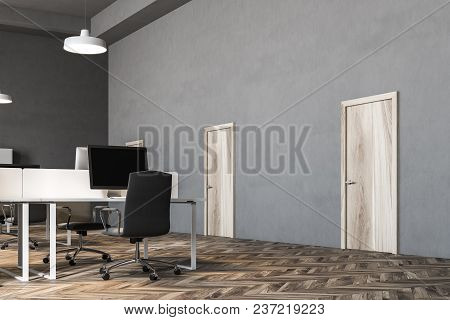 Black Chairs Open Office Interior With A Wooden Floor, Rows Of Computer Desks And Black Office Chair
