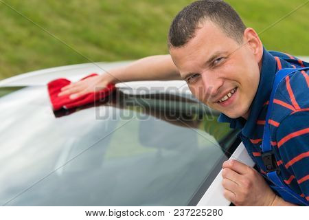 Handsome Man Wipes The Car With A Rag