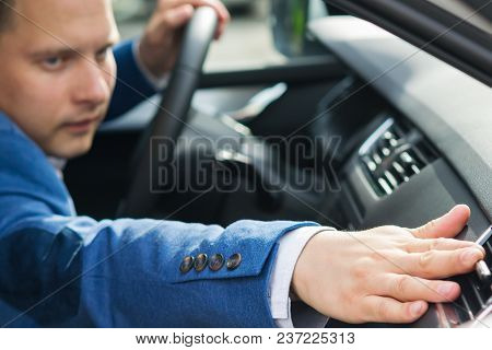 Man In A Blue Suit Adjusts The Air Intake In The Car