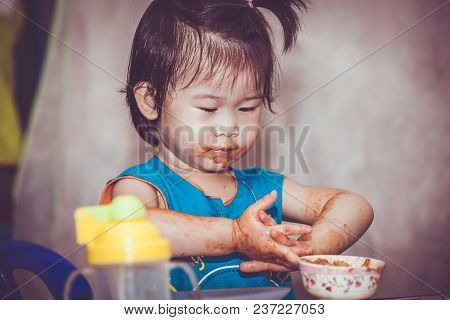 Portrait Of A Asian Child Enjoy Eating. Her Hand And Mouth Get Stained With Ketchup. Charming Girl P