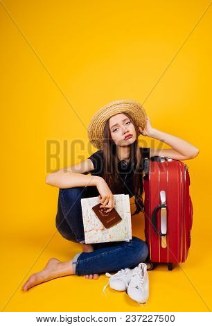 Sad Tired Girl In A Hat Is Waiting For Her Flight For A Long Time, With A Large Suitcase