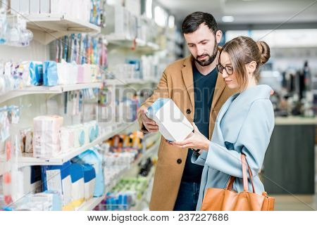 Young Couple Dressed In Coats Choosing Medicine Standing With Box In The Pharmacy Store