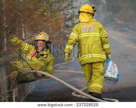 Melbourne, Australia - April 13, 2018: Fire Fighters At A Fence During A Bush Fire In An Suburban Ar