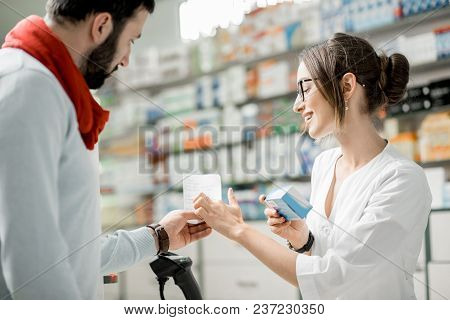 Client Showing Shopping List For The Pharmacist Standing At The Paydesk Of The Pharmacy Store