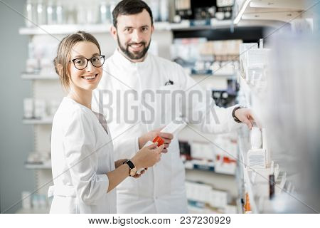 Woman And Man Pharmacists Supervising Medicaments In The Pharmacy Store